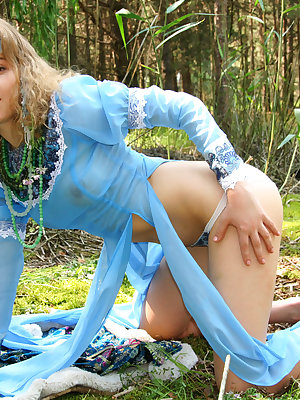 This image set is about a gorgeous blonde teen who takes off her blue dress to do a stirring tease show in the woods.