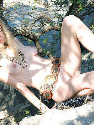 Soft skin, sunbathed hot cliff, a beautiful naked blonde. Adorable girl showing her astonishing delicate artistic loveliness.