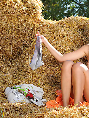 Fascinating teen charmer taking off clothes and spreading legs outdoors on the haystack.
