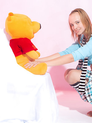 Wonderful teen beauty in striped gaiters with a teddy bear undressing and spreading legs.