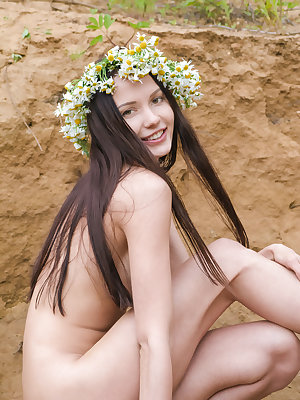 Incredible busty teen hottie with a wreath of daisies on her head showing body in a sand pit.