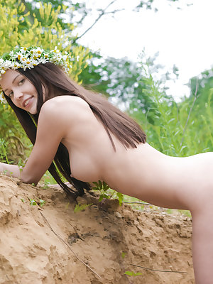 Adorable busty teen girl posing in only a wreath of daisies on her head in a sand quarry.