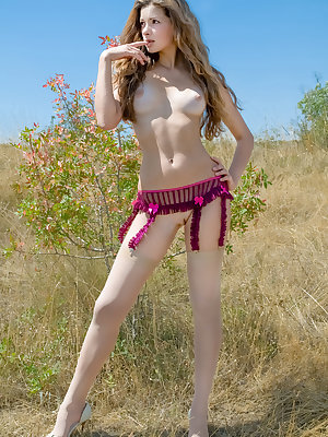 Entrancing teenage girl with a stunning face and amazing slim body poses naked outdoors.