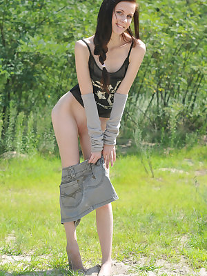 Lovely teen babe strips down outdoors to flash her nice small titties and shaven pussy.