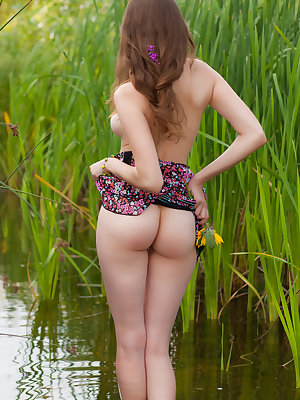 Entrancing teen takes off her dress by the river and exposes her perfectly shaped nude body.