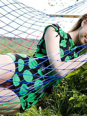 Cute teen girl lounges in a hammock and shows us she wears nothing underneath her dress.