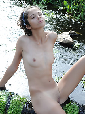 Charming petite girl posing naked by the river and spreading her pussy lying in the water.