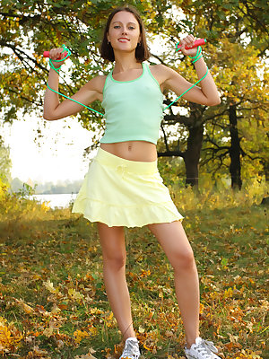 Slim teen girl takes off green top, yellow skirt and white panties.