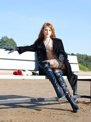 Girl in black coat and sexy high-heel boots poses on the bench now.