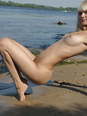 Nothing in the world can be compared with this nude attractive beauty as she is posing on the rocks of the blue river.