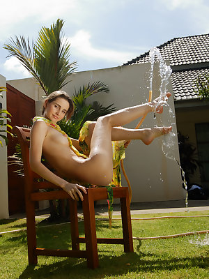 Long-haired cutie with amazingly hot body teases you playing with water at the backyard.