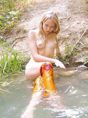 This marvelous nude blonde feels like a fish in water when you look how skillful she poses in the cold river in the forest.