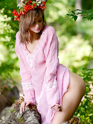 Fabulous nude kitten is sitting in the forest in bright read garland and poses energetically in front of the camera.