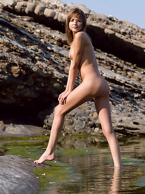 Good-looking nude angel poses at the seaside on the rocks in white peaked cap and blue panties.