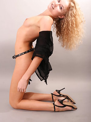 Thrilling incredible kitten with beautiful locks in a sexy black unbuttoned shirt and leather belt poses in the grey background.