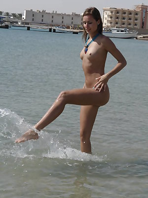 Incredible astounding nude beauty is lying in the water at the seaside and gaily smiles in the objective of the camera.