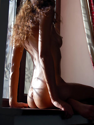 Hot long-haired brunette caresses her juicy tits and extremely wet pussy on brown windowsill.