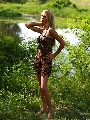 Charming blond is standing in the forest near a lake and looks like a real lioness in leopard dress, which the angel slowly take