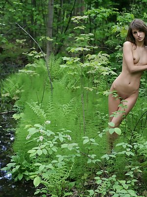 Nude girl walking along a forest, hiding in bushes and even climbing on trees
