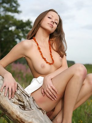 Naked brunette strolling along the forest and showing essence of her beauty