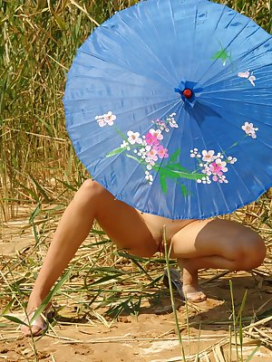 Girl in a light dress strolling outdoors, hiding from the sun under the sunshade and stripping
