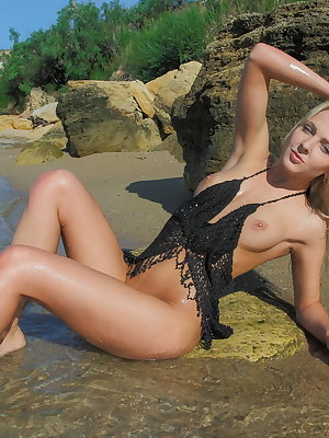 Blonde babe enjoying the sunshine on the beach as it burns all of her naked body and flawless boobs.