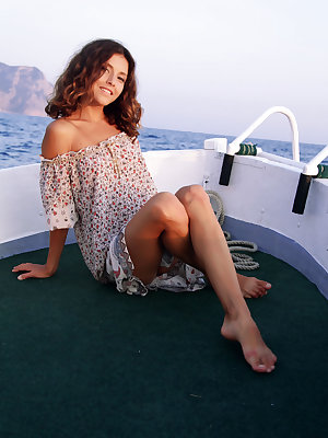 A hot slim brunette with a cute smile sensually takes off her clothes and caresses her soft skin while on a boat trip.