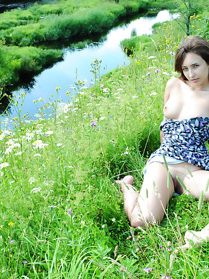 Busty beauty queen enjoys the warm sunshine beside crystal clear creek. Natural beauty in natural environment. The best combination.