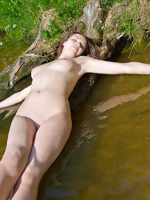 She is looking like just jumped out of the fairy tales. Supernatural busty brunette playing in shallow water of idyllic lake.