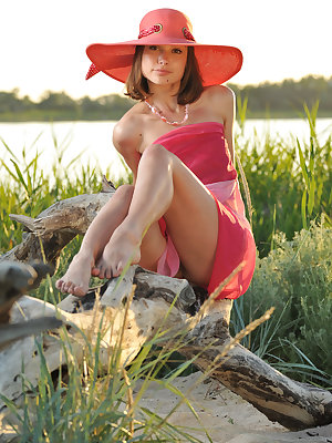 Enchanting girl in a hat with a wide brim showing her perfect body outdoor on the coast.