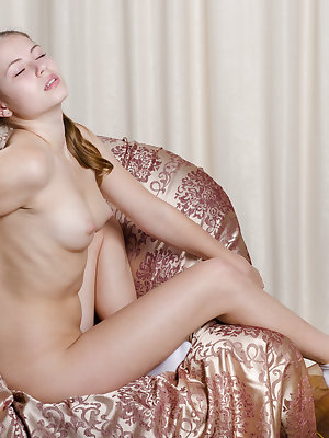 Delightful charmer taking off clothes and demonstrating inviting holes on the armchair.