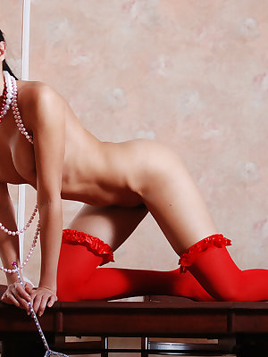 Amazing brunette girl in tempting red stockings demonstrating excellent body on the table.