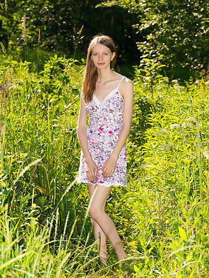 Amazing cutie undressing and posing in the nude outdoor in the field on the plastic sheeting.