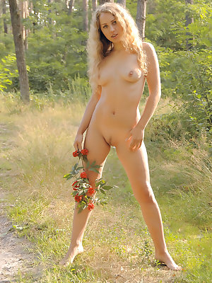 Enchanting long haired fairy posing absolutely naked with a rowan branch in the autumn forest.