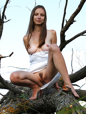 Gorgeous long haired honey taking off her clothes and posing absolutely naked outdoors.