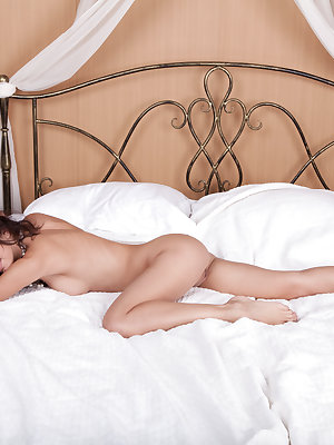 Perfect brown eyed beauty seductively poses naked in the bedroom showing off her pussy.