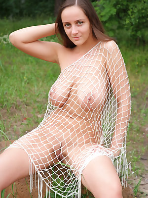 Fabulous busty babe exposes her awesome nude body covered with just a fishnet outdoors.