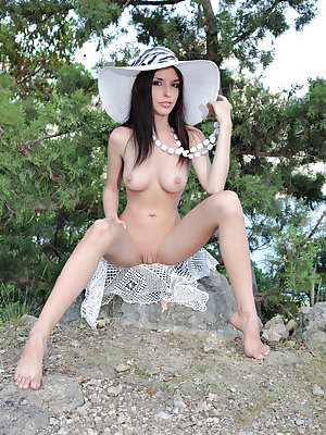 Slim and graceful brunette hottie poses outdoors wearing just a necklace and a wide hat.