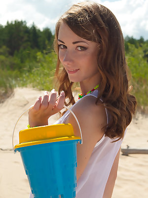 Petite brunette gets naked on the beach and plays with the sand and her amazing body that shines bright in the sun.
