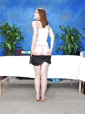 Redheaded teen stripping at the massage table and showing puffy ass
