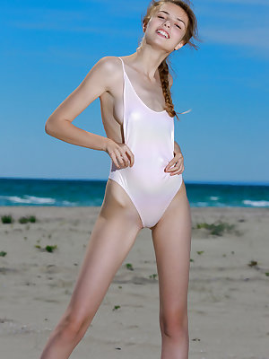 Thin teen girl Elle Tan slips out off her bathing suit to model nude on beach