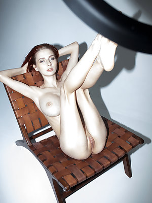 Thin redhead Helga Grey fondly displays her huge boobs and hairless pussy