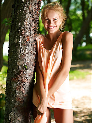 Smiley cute teen in short dress disrobes to pose nude under a tree
