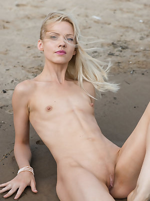 Blonde solo model slips off her dress and panties at the beach