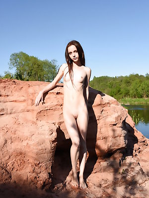 Naked young girl displays her thin body on a path and rock by a pond