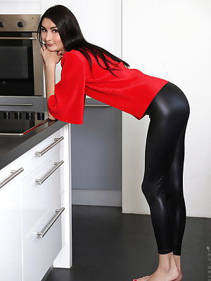 Dark haired girl Bambi Jolie removes her leather pants before toying her pussy