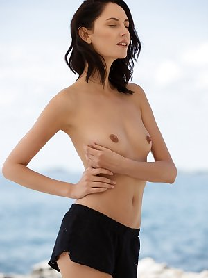 Dark haired female Sade Mare bares her small tits at water's edge