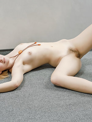 Young redhead poses her pliable body in the nude on her bed
