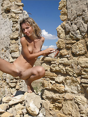 Skinny blonde chick wanders among ancient runes in the nude