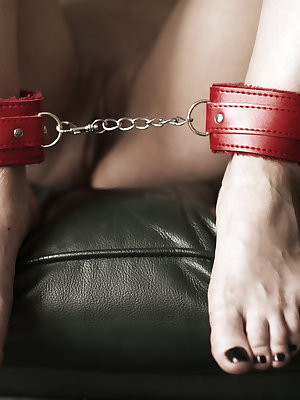 Erotic fetish model Lola S in red lingerie fingers her pussy in handcuffs